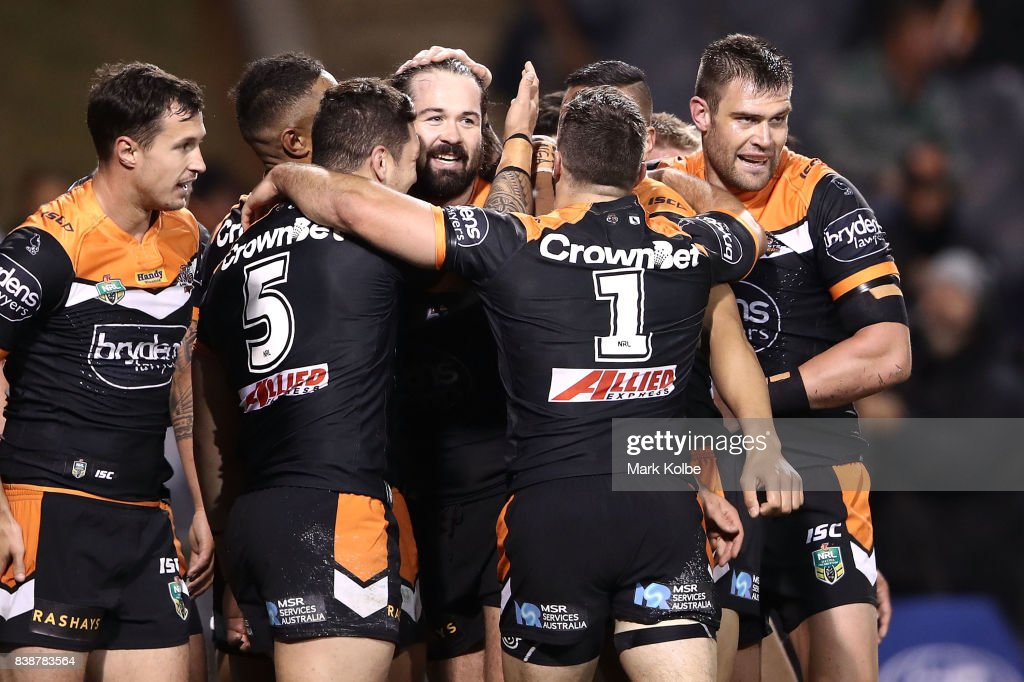 Aaron Woods of the Tigers celebrates with his team after scoring a try during the round 25 NRL match between the Wests Tigers and the North Queensland Cowboys at Campbelltown Sports Stadium on August 25, 2017 in Sydney, Australia.
