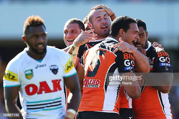 Aaron Woods of the Tigers celebrates with team mates after scoring during the round two NRL match between the Wests Tigers and the Penrith Panthers...
