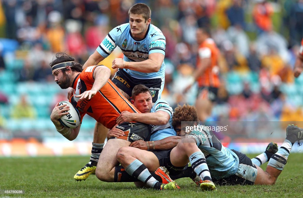 Aaron Woods of the Tigers is tackled by Blake Ayshford, Scott Sorensen and Sione Maima of the Sharks during the round 26 NRL match between the Wests Tigers and the Cronulla Sharks at Leichhardt Oval on September 6, 2014 in Sydney, Australia.