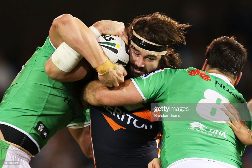 Aaron Woods of the Tigers is tackled by David Shillington of the Raiders during the round 16 NRL match between the Wests Tigers and the Canberra Raiders at Campbelltown Sports Stadium on June 28, 2014 in Sydney, Australia.