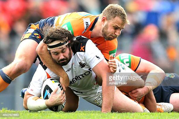 Aaron Woods of the Tigers is tackled by Knights defence during the round 13 NRL match between the Newcastle Knights and the Wests Tigers at Hunter...
