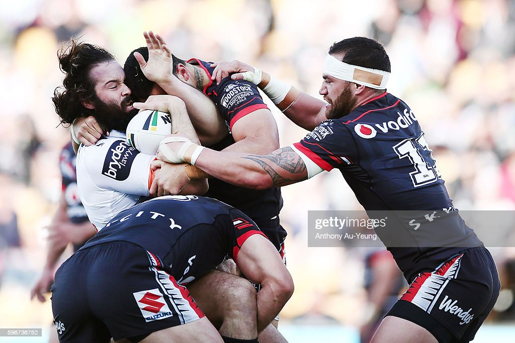 Aaron Woods of the Tigers is tackled by Simon Mannering and Bodene Thompson of the Warriors during the round 25 NRL match between the New Zealand Warriors and the Wests Tigers at Mount Smart Stadium on August 28, 2016 in Auckland, New Zealand.