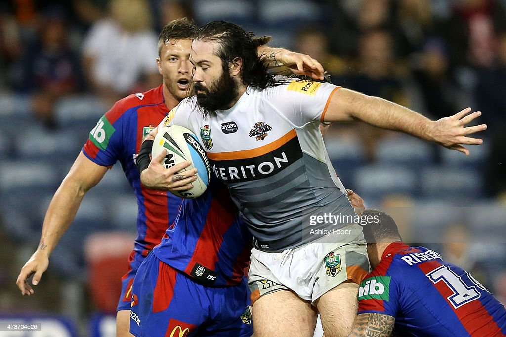Aaron Woods of the Tigers is tackled by the Knights defence during the round 10 NRL match between the Newcastle Knights and the Wests Tigers at Hunter Stadium on May 17, 2015 in Newcastle, Australia.