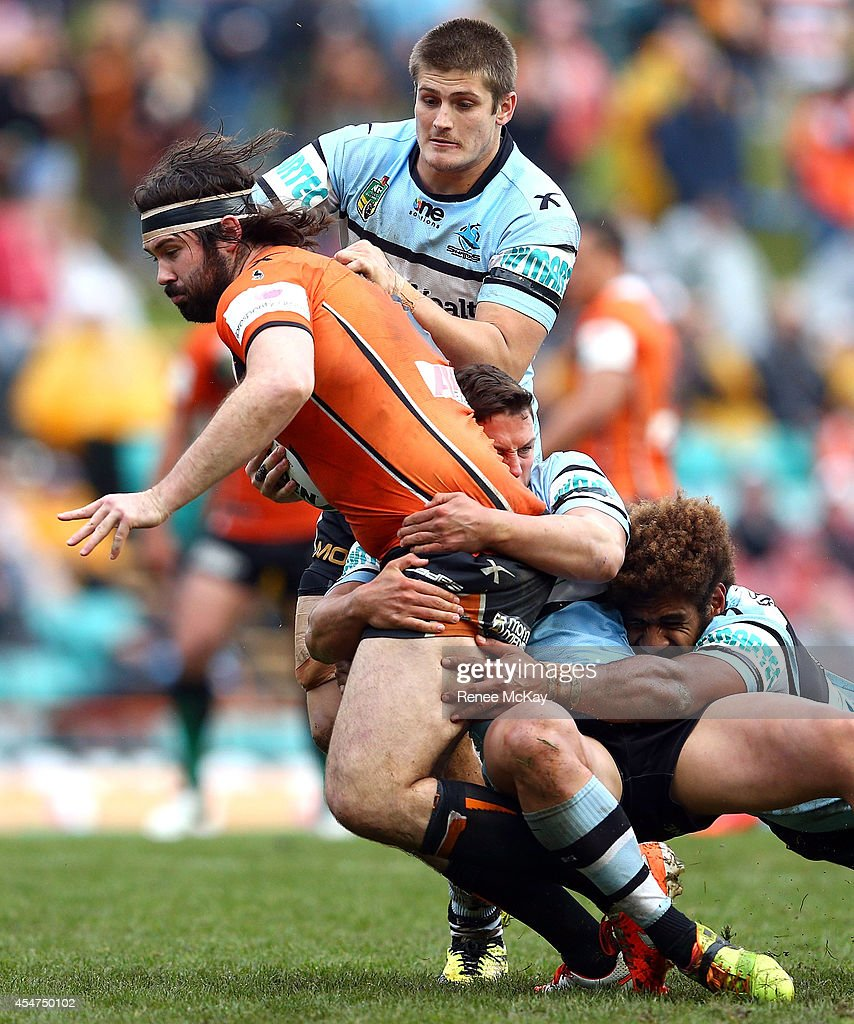 Aaron Woods of the Tigers is tackled by the Sharks defence during the round 26 NRL match between the Wests Tigers and the Cronulla Sharks at Leichhardt Oval on September 6, 2014 in Sydney, Australia.
