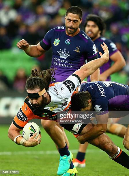 Aaron Woods of the Tigers is tackled during the round 16 NRL match between the Melbourne Storm and Wests Tigers at AAMI Park on June 26 2016 in...
