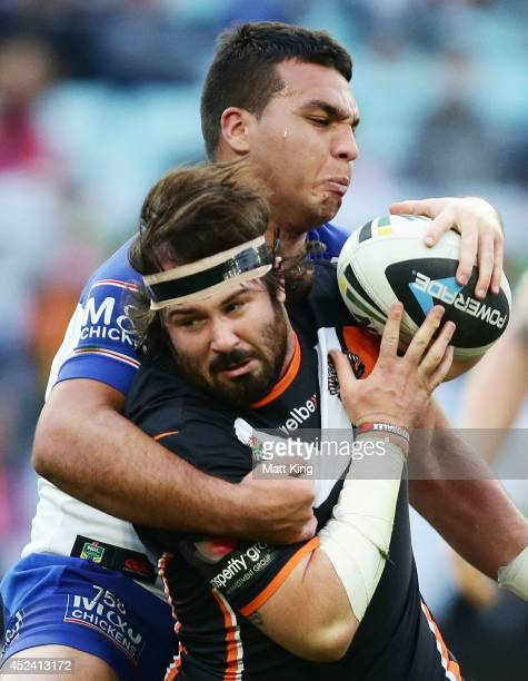 Aaron Woods of the Tigers is tackled during the round 19 NRL match between the Wests Tigers and the Canterbury Bulldogs at ANZ Stadium on July 20...