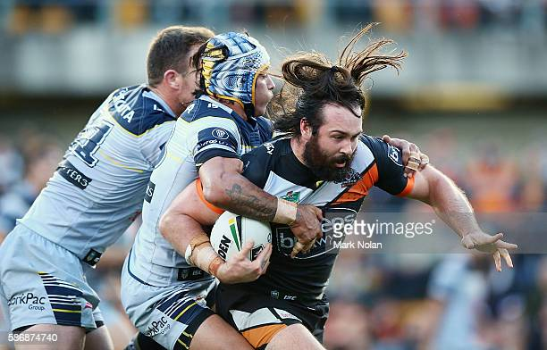 Aaron Woods of the Tigers is tackled during the round 22 NRL match between the Wests Tigers and the North Queensland Cowboys at Leichhardt Oval on...
