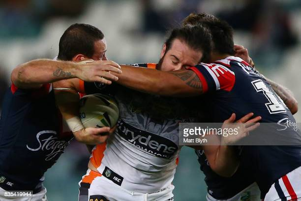 Aaron Woods of the Tigers is tackled during the round 24 NRL match between the Sydney Roosters and the Wests Tigers at Allianz Stadium on August 19...