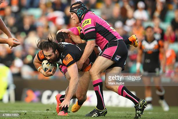 Aaron Woods of the Wests Tigers is tackled by Nigel Plum of the Panthers during the round 16 NRL match between the Wests Tigers and the Penrith...