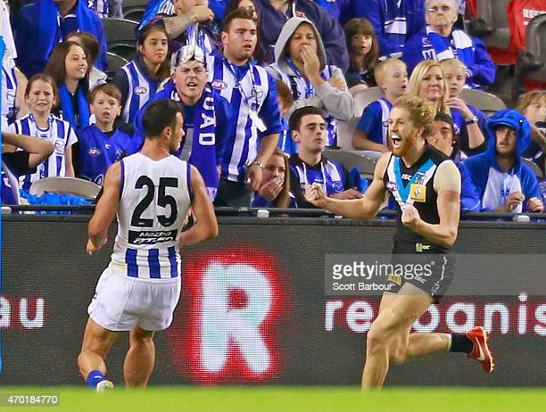 Aaron Young of the Power celebrates after kicking a goal in the final quarter as dejected Kangaroos supporters in the crowd look on during the round...