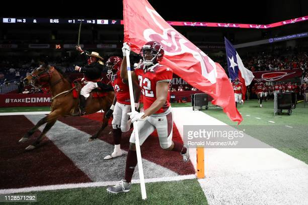 AaronGreen of the San Antonio Commanders carries a San Antonio Commanders flag as he runs onto the field prior to an Alliance of American Football...