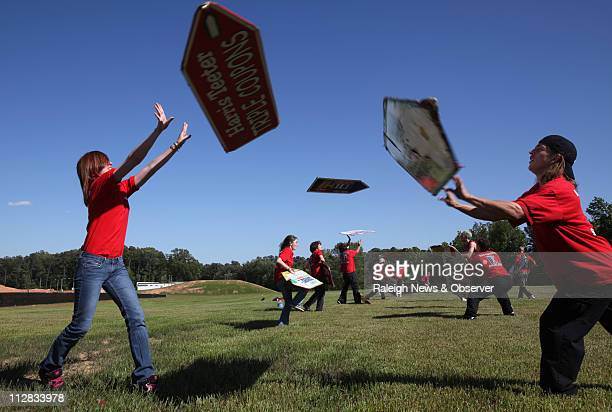 AArow Advertising sign spinners including Jessica Liscum of Raleigh left and Duane Billington of Cary exchange a sign at a weekly practice session at...