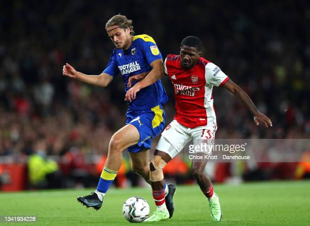 Aarson Pressley of AFC Wimbledon and Ainsley Maitland Niles of Arsenal battle for the ball during the Carabao Cup Third Round match between Arsenal...