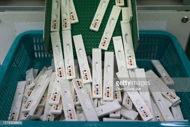 Ab testing kits Ichroma Covid19 Ab used in diagnosing the coronavirus fall into a basket at the Boditech Med Inc headquarters on April 17 2020 in...