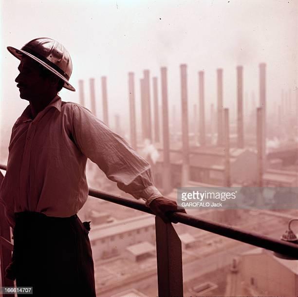 Abadan Refinery In Iran Abadan fin des années 50 Un ouvrier portant un casque de protection posant devant les cheminées d'une raffinerie de pétrole