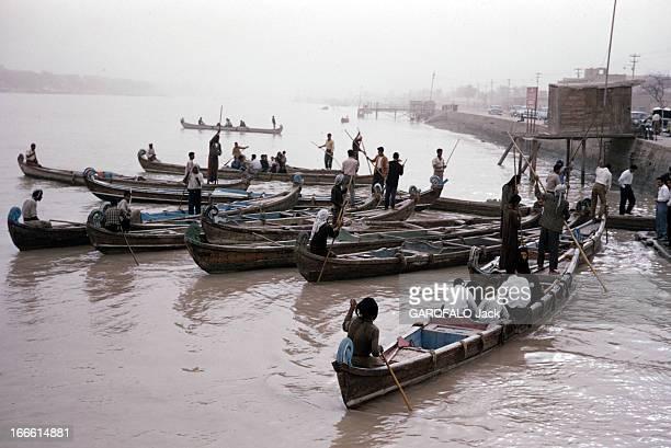 Abadan Refinery In Iran Iran fin des années 50 Sur une rivière un groupe de personnes dans des barques accostant près d'une route
