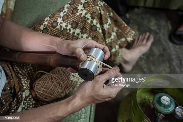 Abah binds the head tube and bamboo with hemp rope in the process of making a bamboo bike frame at Haur Bike workshop on June 19 2013 in Bandung Java...