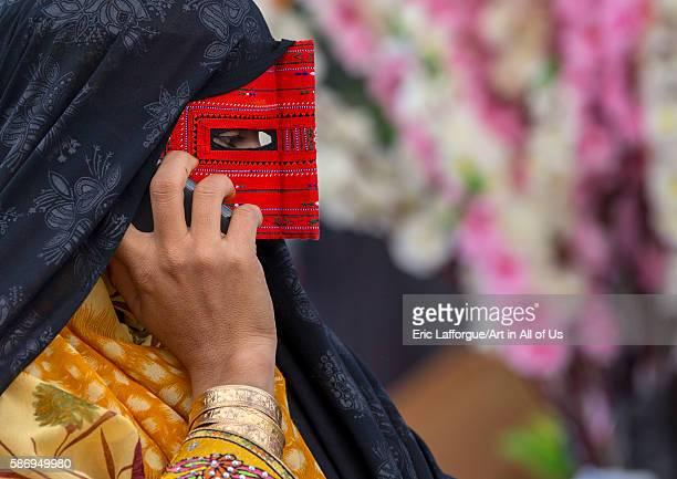Abandari woman wearing a traditional mask called the burqa calling on a mobile phone hormozgan minab Iran on December 31 2015 in Minab Iran