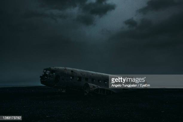 abandoned airplane wreck on a barren nordic wilderness against a gloomy sky - airplane crash stock pictures, royalty-free photos & images