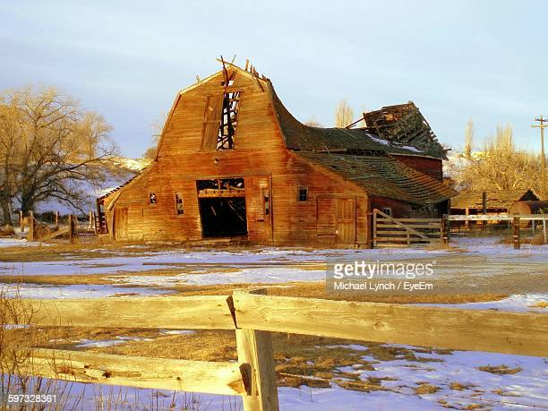 Abandoned Barn On Snow Covered Field Against Sky