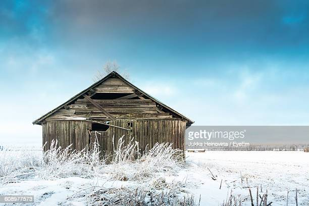 abandoned barn on snow covered field against sky - heinovirta stock photos and pictures