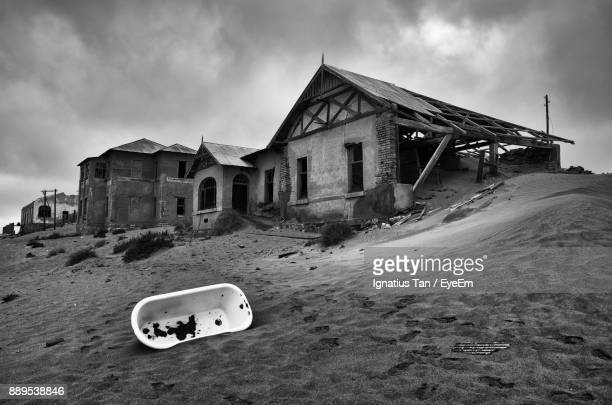 abandoned bathtub on sand by hut against sky - ignatius tan stock photos and pictures