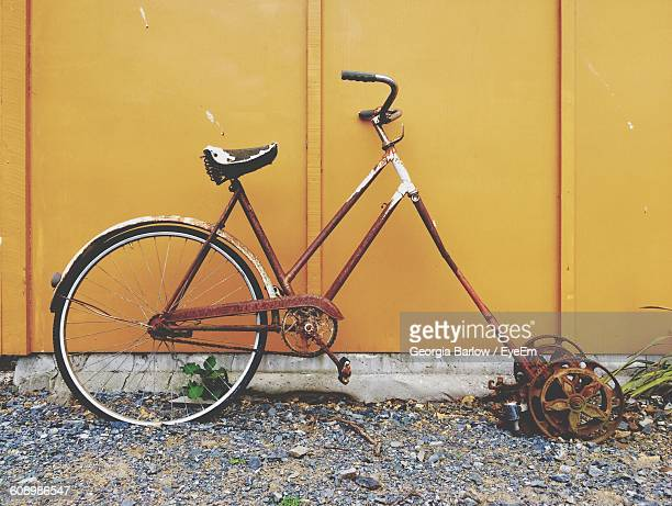 Abandoned Bicycle Against Yellow Wall