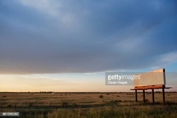 Abandoned billboard on grassy field against cloudy sky