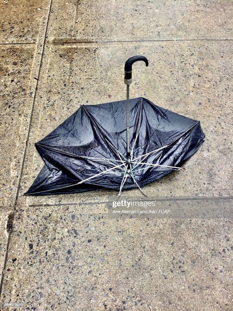 Abandoned black umbrella on street : Stock Photo