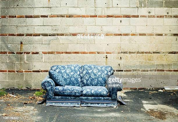 A l'abandon Blue canapé assis contre le mur de ciment à l'extérieur