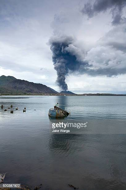 Abandoned boat and Volcano, Mt. Tavurvur, Rabaul, Papua New Guinea