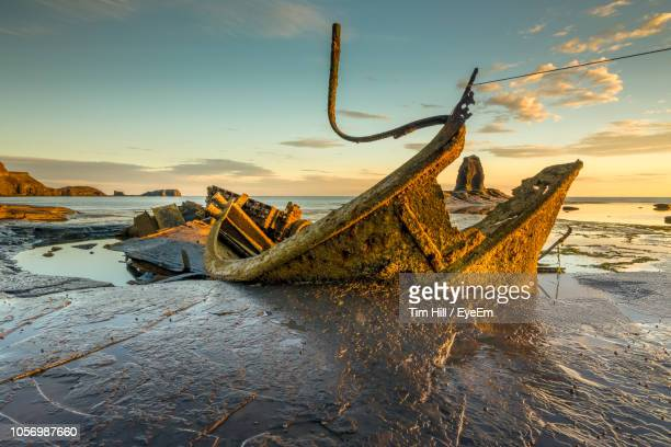abandoned boat at beach against sky during sunset - shipwreck stock pictures, royalty-free photos & images