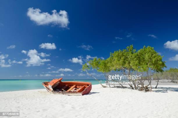 abandoned boat at palm beach, aruba - aruba stockfoto's en -beelden