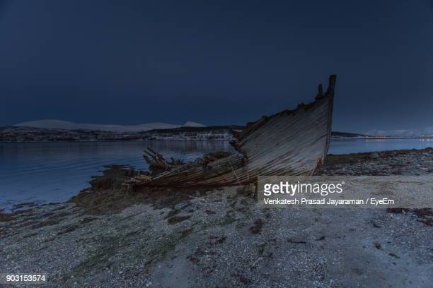Abandoned Boat At Riverbank During Dusk