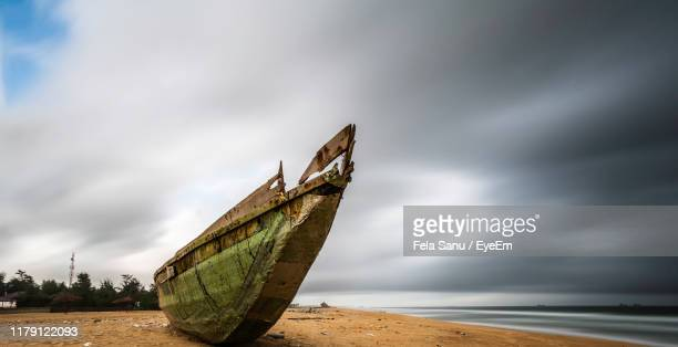 abandoned boat moored on beach against sky - lagos nigeria photos et images de collection