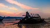 Abandoned Boat on Beach with Sea and Dramatic Sky