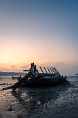 Abandoned Boat on Beach with Sea before Sunrise