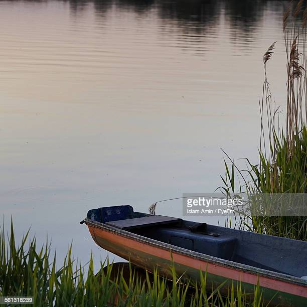 Abandoned Boat On Riverbank By Grass