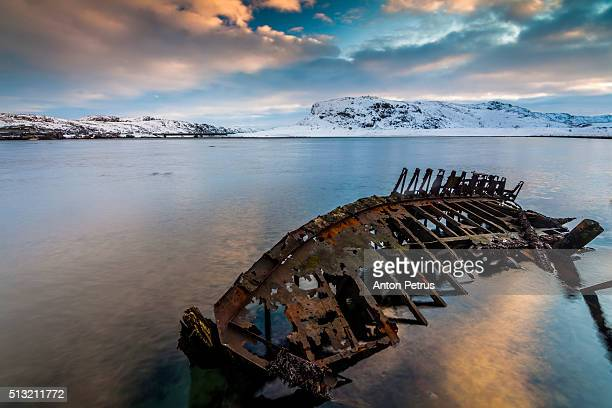 Abandoned boats in the water at sunset