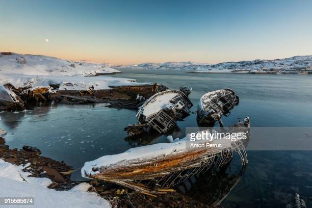 Abandoned boats in the water at winter sunset