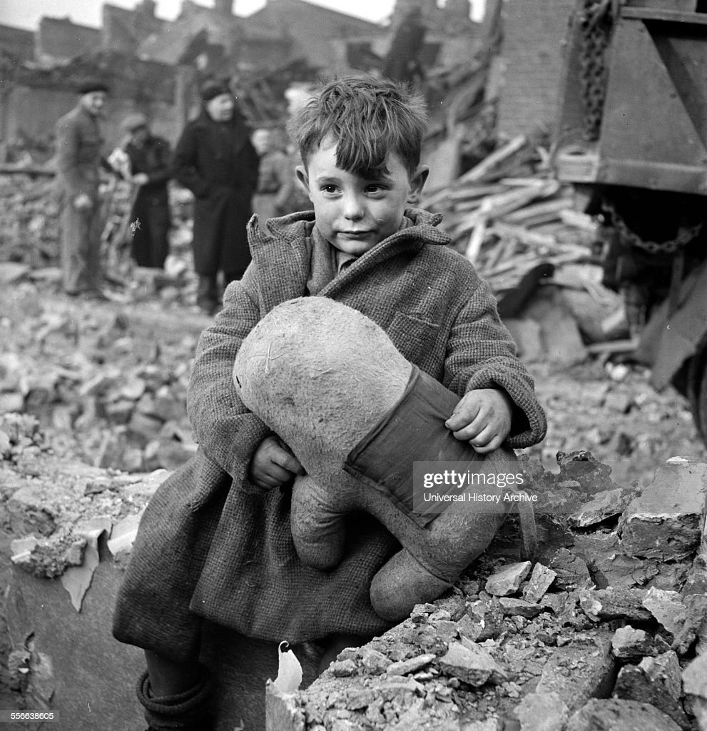 Abandoned boy holding a stuffed toy animal amid ruins following German aerial bombing of London during the Blitz of World War two.