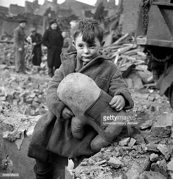 Abandoned boy holding a stuffed toy animal amid ruins following German aerial bombing of London during the Blitz of World War two
