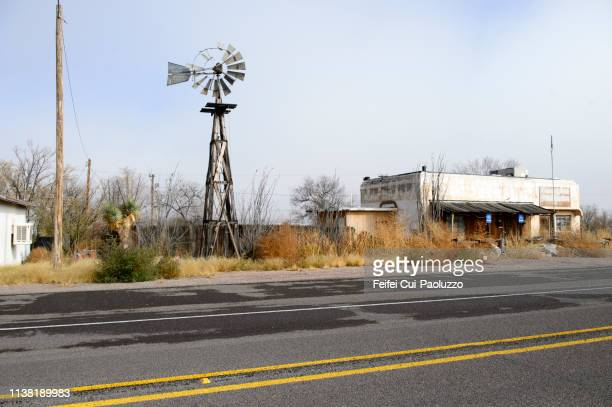 abandoned building and traditional windmill at sierra blanca, texas, usa - small town america stock pictures, royalty-free photos & images