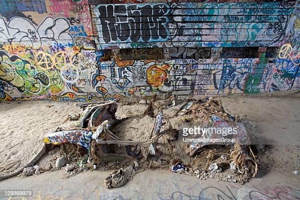 Abandoned car and graffiti underneath bridge in the Los Angeles River, California, USA.