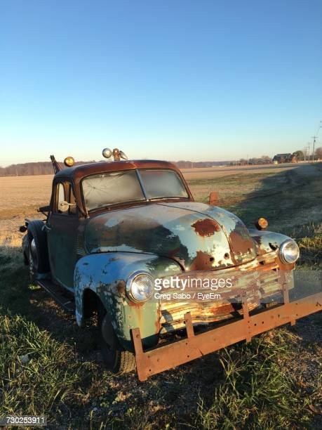 Abandoned Car On Field Against Clear Blue Sky
