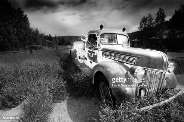 Abandoned Car On Grassy Field Against Sky