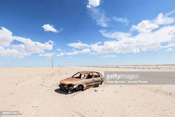abandoned car wreck sitting in namib desert, swakopmund, erongo region, namibia - abandoned car stock photos and pictures