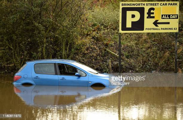 Abandoned cars are pictured in a flooded car park in Rotherham northern England on November 8 following flash flooding yesterday Over a month's worth...