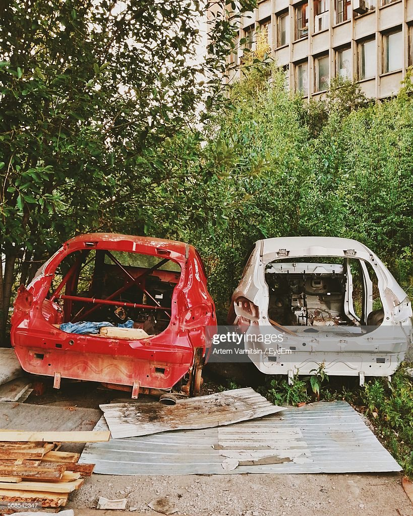 Abandoned Cars By Trees And Building : Stock Photo