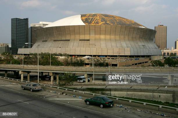 Abandoned cars remain on Interstate 10 in front of the heavily damaged Superdome September 14 2005 in New Orleans Louisiana After being damaged by...